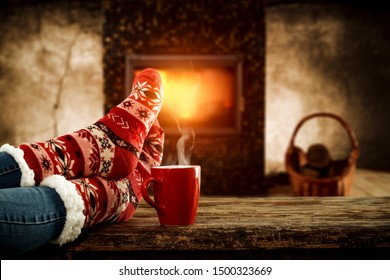 Woman legs with christmas socks and home interior with fireplace and dark wall background. Free space for your decoration.