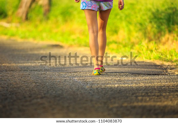Woman legs in colorful shoes walking after running fast training outdoor. Healthy active lifestyle concept. Fit young woman running in the park. Female runner jogging down an outdoor trail.