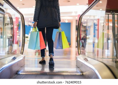 Woman legs with colorful shopping bags on the escalator in a shopping mall