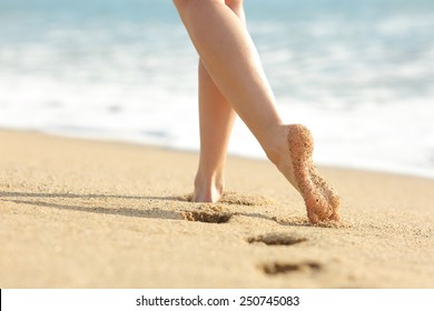 Woman legs and feet walking on the sand of the beach with the sea water in the background