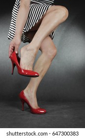 Woman legs and feet wearing  dress putting on  shoes over grey background