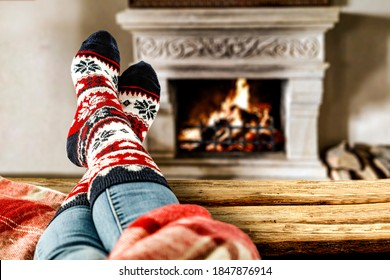 Woman legs and fireplace in home interior