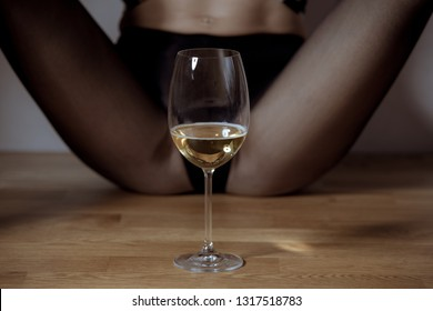 Woman legs and a glass of beverage