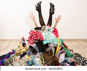 Woman legs and hands reaching out from a big pile of clothes and accessories.Woman buried under an untidy cluttered woman wardrobe.Woman in high heels needs help from to much shopping.Shopaholic girl.