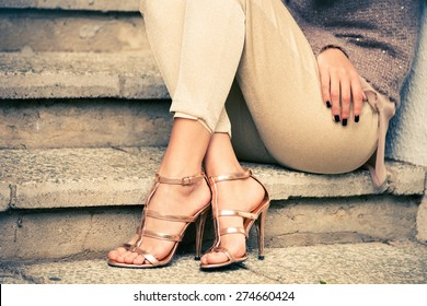 woman legs in high heel golden sandals sit on stairs, outdoor shot