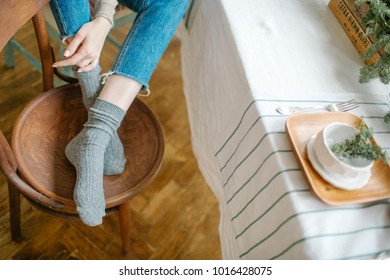 Woman legs in jeans on the chair in front of dining table