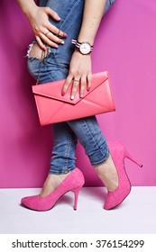 Woman legs in jeans with pink handbag and high heels shoes . Pink background . Trendy accessories watch