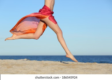 Woman legs jumping on the beach happy with the horizon and sea in the background
