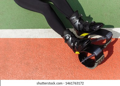 Woman legs in the Kangoo jumps shoes. Sport equipment