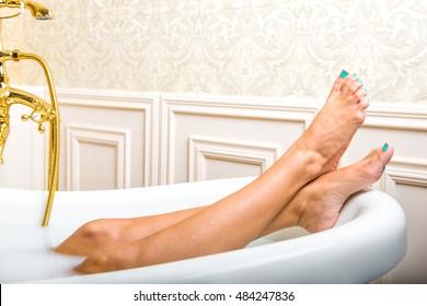 Woman legs lying in white bathtub
