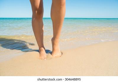 Woman legs on seashore