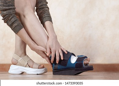 Woman legs, one in bandage and orthopedic boot after trauma or surgery.  The result of using tigh shoes, deformity of great toe or first metatarsophageal joint, hallux valgus or bunion. Copy space.