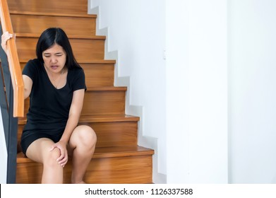 Woman legs pain with touching her knee and walking up stairs at home