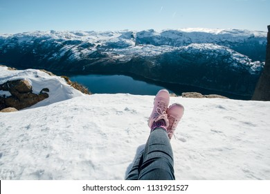 Woman legs in pink boots. Woman sitting on the snow. Scenic landscape of river channel, sea between rocky shore with snow. Top view of the Pulpit Rock, Preikestolen. Lysefjord, Norway