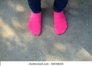 Woman legs in pink sock on concrete floor with sunlight.