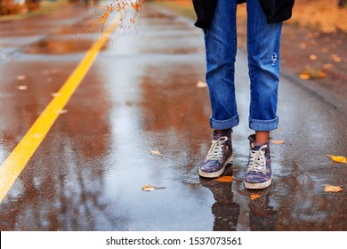 woman legs in puddles in autumn