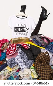 Woman legs reaching out from a big pile of clothes with a t-shirt saying nothing to wear. Girl buried under an untidy cluttered wardrobe. Woman in high heels and to much shopping. Shopaholic girl.