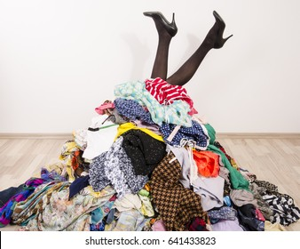 Woman legs reaching out from a big pile of clothes and accessories. Woman buried under an untidy cluttered woman wardrobe. Woman in high heels needs help from to much shopping. Shopaholic girl.