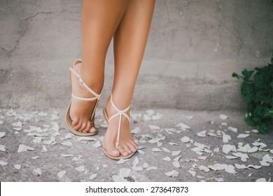 Woman legs with rose petals. Beautiful female feet