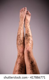 Woman legs with scrub coffee grounds. Body care concept. Colorized