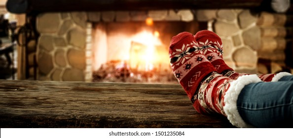 Woman legs with socks and christmas fireplace