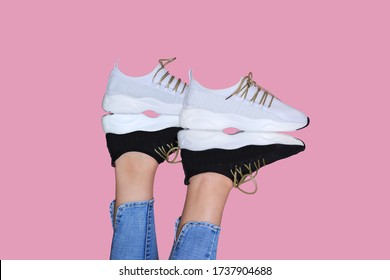 Woman legs in sporty sneakers upside down. Black and white two pairs of shoes. Creative design.