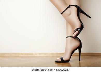 woman legs in stylish black heels, studio white