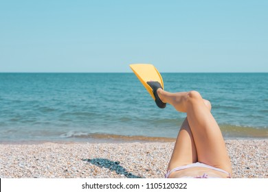 Woman legs with swim flippers on a sand beach. Funny image with woman legs wearing swim flippers over blue sky and the sea