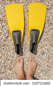Woman legs with swim flippers on a sand beach, top view, view from above