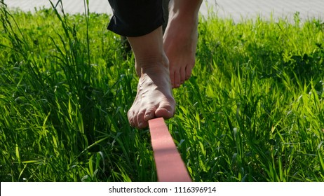 Woman legs walk along a tight line in a city park. Girl of the foot balances on slackline, goes back close-up