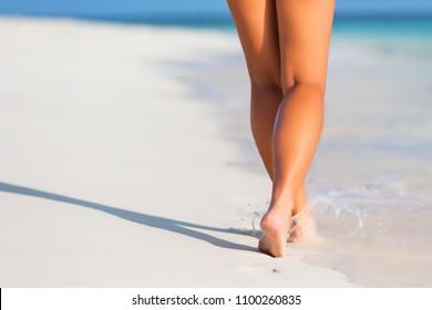 Woman legs walking on the beach sand