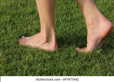 Woman legs walking on green grass, closeup barefoot walking