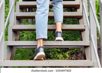 Woman legs walking up on stairs in summer park. Outdoor sport, walking concept. Close-up, copy space