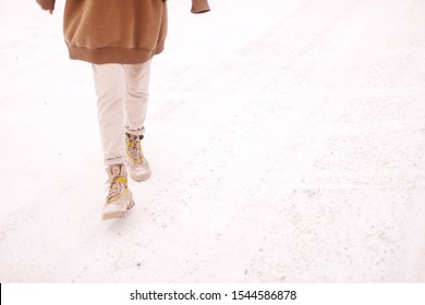 Woman legs in warm boots stand on a snowy footpath, on a winter frosty day. Woman walking in snow day. Girl wear brown hoodie and beige pants, boots with yellow laces.