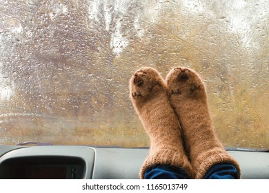 Woman legs in warm cute kawaii socks on car dashboard. Drinking warm tee on the way. Fall trip. Rain drops on windshield. Freedom travel concept. Autumn weekend