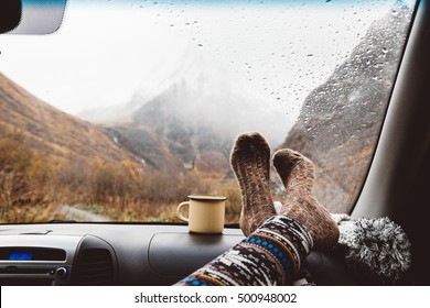 Woman legs in warm socks on car dashboard. Drinking warm tee on the way. Fall trip. Rain drops on windshield. Freedom travel concept. Autumn weekend in mountains.