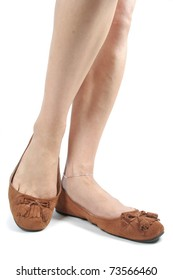 Woman legs wearing brown moccasin shoes