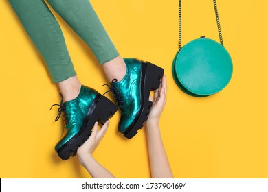 Woman legs wearing green shoes with black heels and a fashion purse. Hands holding the footwear. Creative design background.