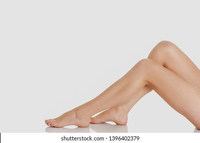 Woman legs while sitting on white background. Depilation concept.