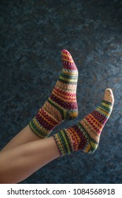 Woman legs in wool knitted socks on a grey background