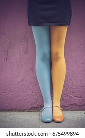 Woman legs with yellow and blue panties and mary jane shoes over a violet wall background - Funny tights and flat shoes - Colorful female legs - Fashion, cute, retro stylish look - Two colors