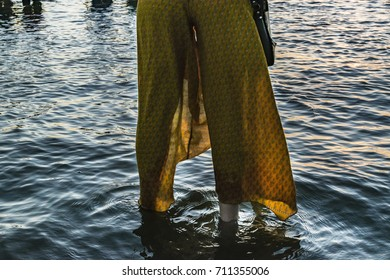 Woman legs with yellow skirt at water at iemanja celebration, Montevideo, Uruguay