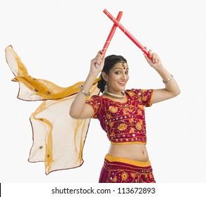 Woman in lehenga choli performing dandiya dance