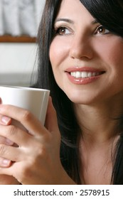 A woman leisurely relaxes with a hot beverage.