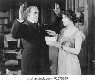 Woman with a letter in her hand pointing at a man