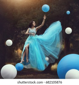 The Woman levitates. A beautiful girl in a blue fluffy gown Leets along with balloons. Fantasy and Surrealism. The girl flies like in a fairy tale. Happy girl in prom with helium air balloons.