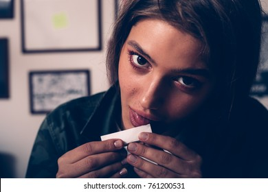 woman licking cigarette paper, preparing to smoke, looking at the camera