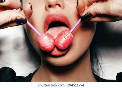 Woman licking two tasty lollipops. Close up against white background, not isolated