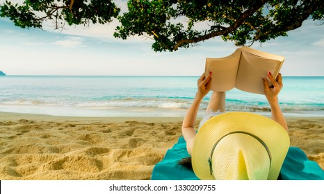 Woman lie down on green towel that put on sand beach under the tree and reading a book. Slow life on summer vacation. Asian woman with hat relaxing and enjoying holiday at tropical beach. Summer vibes