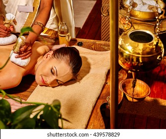 Woman lie on stomach having ayurvedic massage with pouch of rice. Shirodhara pot for head massage on foreground.
